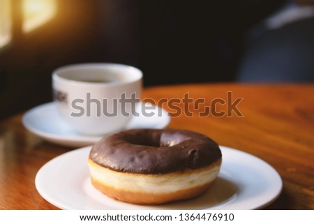Fresh chocolate donut with coffee on the wooden table in cafe. #1364476910