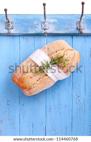 Fresh Ciabatta (Italian bread) is hanging headlong on a hook on a blue wooden board, ciabatta bread ready for sale