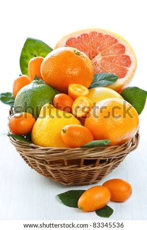 Fresh citrus fruit with leaves in a wicker basket.
