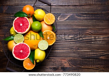 Fresh citrus fruits in basket. Orange, grapefruit, lemon, lime, tangerine on dark wooden table. Assorted fresh citrus fruits with leaves. Top view and copy space #773490820