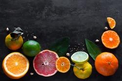 Fresh citrus fruits (orange, mandarin, lemon, lime, grapefruit) on a black background with place for text. concept vitamins for immunity