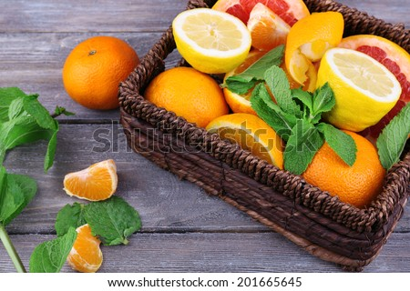 Fresh citrus fruits with green leaves in wicker basket on wooden background #201665645