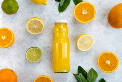 Fresh citrus juice in glass bottle. Summer drink, orange, lemon and lime on light background. Vitamin C, healthy lifestyle, diet. Top view, flat lay