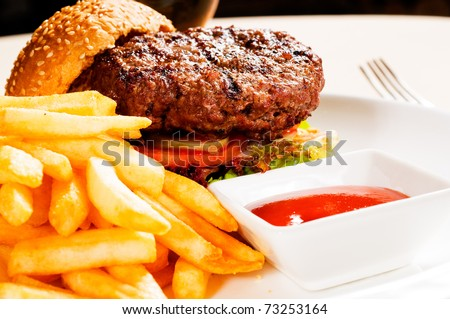 fresh classic american hamburger sandwich with french fries and ketchup sauce on side