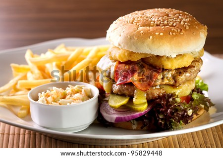 fresh classic american hamburger sandwich with french fries and sauce on side