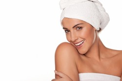 Fresh clean portrait of a beautiful vivacious smiling woman full of vitality wrapped in bath towels isolated on white for a personal hygiene, spa treatment of health and wellbeing concept