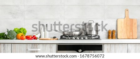 Fresh clean vegetables being put on a kitchen desk top, ready for cooking, front view of modern kitchen countertop with domestic culinary utensils on it, home healthy cooking concept banner Stockfoto ©