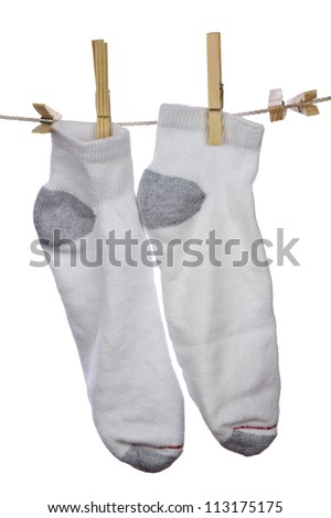 Fresh clean white cotton socks hanging and drying on clothesline on white background.