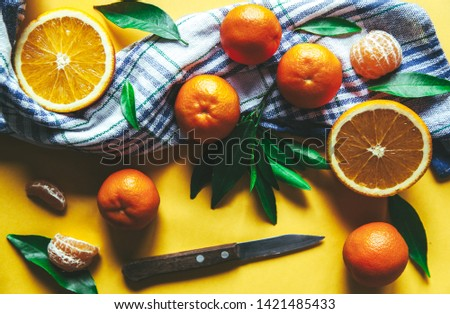 Fresh clementines, oranges on board with green leaves with a knife. Top view on a yellow background #1421485433