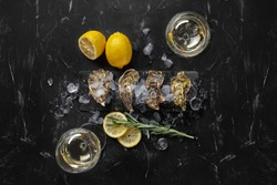 Fresh closed oysters, ice, lemon on a rectangle slate and champagne are on a black stone textured background. Top view with copy space. Close-up.