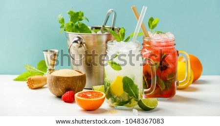 Fresh cocktail drinks with ice fruit and herb decoration. Alcoholic non-alcoholic drink-beverage. Mojito on blue background #1048367083