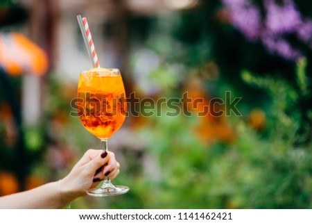 Fresh cocktail in wine glass outdoor against blurred background. Woman holds summer cold drink with ice. Horizontal shot. Tasty acoholic beverage