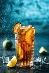 Fresh cocktail with cola, lime, orange and ice in glass on dark blue background. Studio shot of drink in freeze motion, drops in liquid splash. Summer cold drink and cocktail