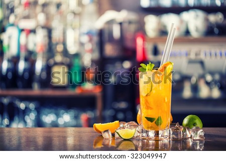 Fresh cocktail with orange, limet, mint and ice. Alcoholic, non-alcoholic drink-beverage at the bar counter in the night club.