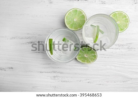 Fresh cocktails with ice and lime on white wooden table background, view from above