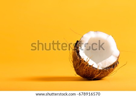 Fresh coconut on a bright yellow background #678916570