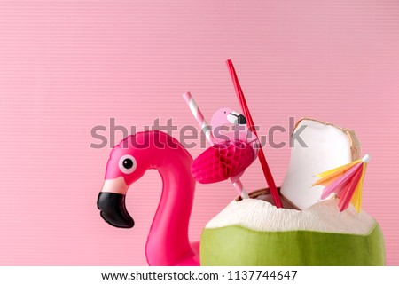 Fresh coconut on a pastel pink background with flamingo inflatable drink holder, summer vibes concept - Shutterstock ID 1137744647
