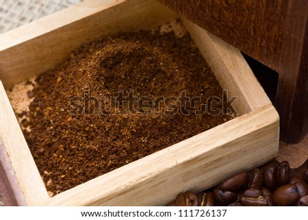 Fresh coffee grinds in coffee grinder box with beans surrounding