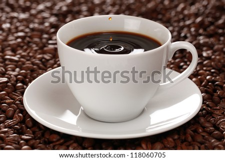 Fresh coffee in a cup with coffee drops.