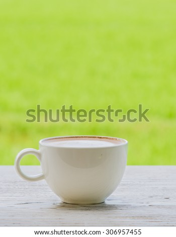 Fresh coffee in a mug shot placed on the left vertical white wooden floor. Behind the green fields blur and poor light.