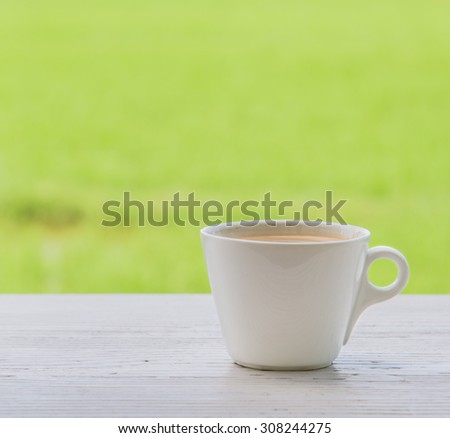 Fresh coffee in a mug shot vertically placed right on the white wood. Behind the green fields blur and poor light.