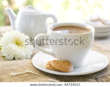 Fresh coffee with milk in cup  with cookie close up. Selective focus