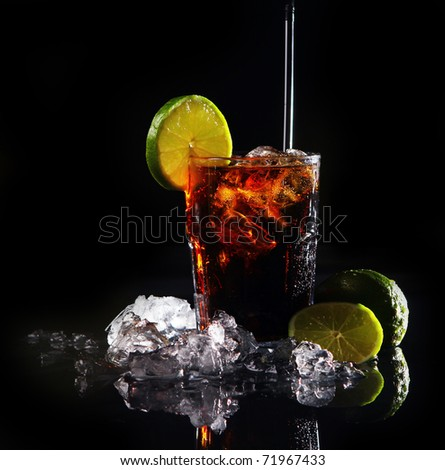 Fresh cola drink with ice and green lime on black background