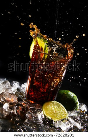 Fresh cola drink with splashesh of water and green lime on black background