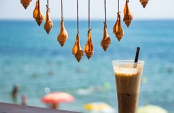 Fresh cold coffee ice milk frappe drink in transparent glass with colorful sea shells hamging on twine string as summer decoration. Blurred background of blue sky, sea water, sunny beach. Relaxation.