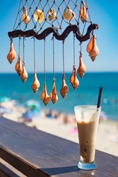 Fresh cold coffee ice milk frappe drink in transparent glass with colorful sea shells hanging on twine string as summer decoration. Blurred background of blue sky, sea water, sunny beach. Relaxation.
