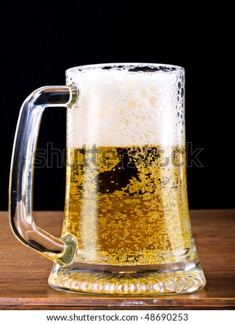 Fresh cold golden light beer with froth served in a glass pint mug on a wooden bar. Closeup shot on black background