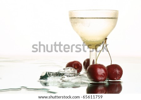 Fresh cold water with ice and cherry. Still-life with refreshment beverage in wineglass on white background