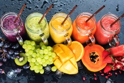 Fresh Color Juices Smoothie Violet Green Yellow Orange Red from Tropical Fruits Kiwi Water Melon Strawberry Apple Orange Banana Pine Apple Mango Pomegranate Grape Bottles Rainbow Dark Background