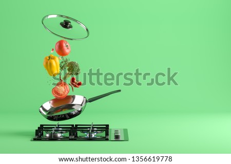 Fresh colored vegetables and glass lid are flying from the frying pan. At the bottom - a cooking stove with burning fire. Green studio background