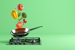 Fresh colored vegetables flying from the stainless steel frying pan. At the bottom - a cooking stove with burning fire. Green studio background