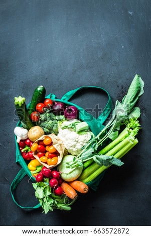 Fresh colorful organic vegetables in green eco shopping bag - captured from above (top view, flat lay). Black chalkboard (blackboard) as background. Layout with free text (copy) space.