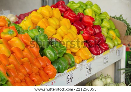 Fresh colorful produce in a Jerusalem fruit and vegetable market: orange, green, red, and yellow bell peppers