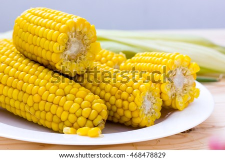 Fresh cooked organic yellow corn on cob kernels on rustic wooden table. Closeup and selective focus. #468478829