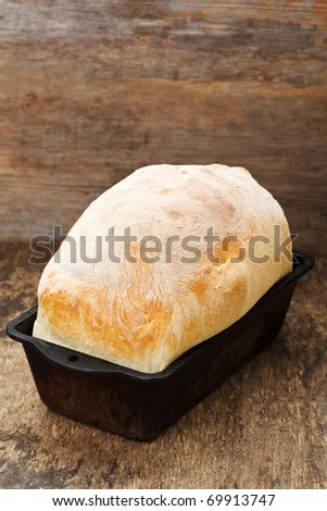 Fresh cooked white bread still in the bread pan