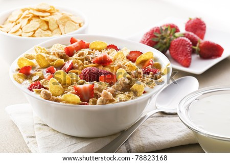 Fresh corn flakes with strawberries and milk close up