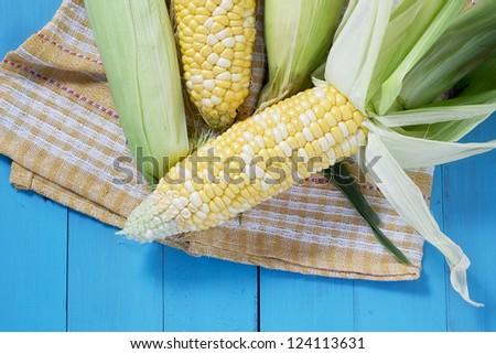 Fresh corn on blue table - stock photo