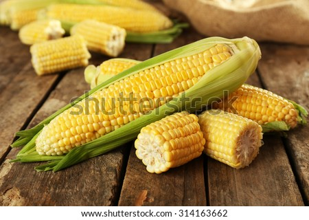 Photo of  Fresh corn on cobs on rustic wooden table, closeup