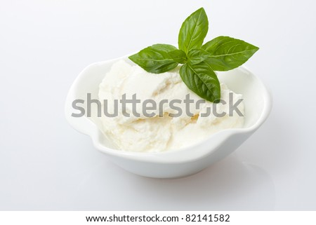 Fresh cottage cheese with basil leaves