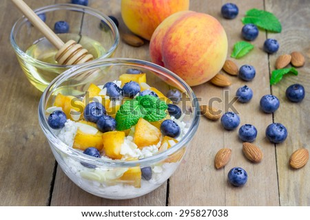 Fresh cottage cheese with peach, blueberry, almonds and honey. Concept of healthy eating for breakfast.