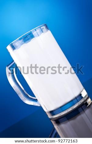 fresh cow milk in a beer mug on blue background