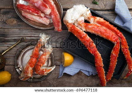 Fresh crab claws on black wooden tray on vintage wooden background with vintage plates and lemon slices. Horizontal composition #696477118