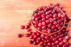 Fresh cranberries in a small basket on a wooden background