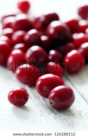 Fresh cranberries on a white wooden surface