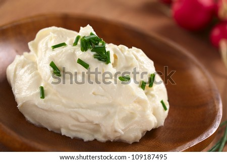 Fresh cream cheese spread on wooden plate with chives on top and radish in the back (Selective Focus, Focus on the chives on the top of the cream cheese)