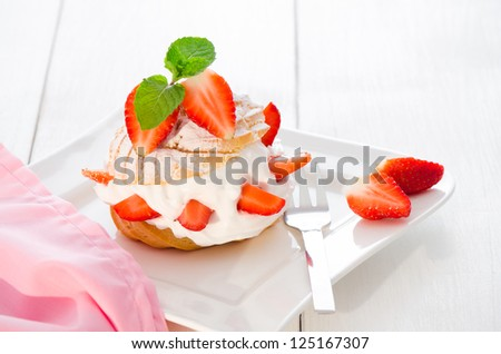 fresh cream puff with whipped cream mint and strawberries on white plate and white wood table